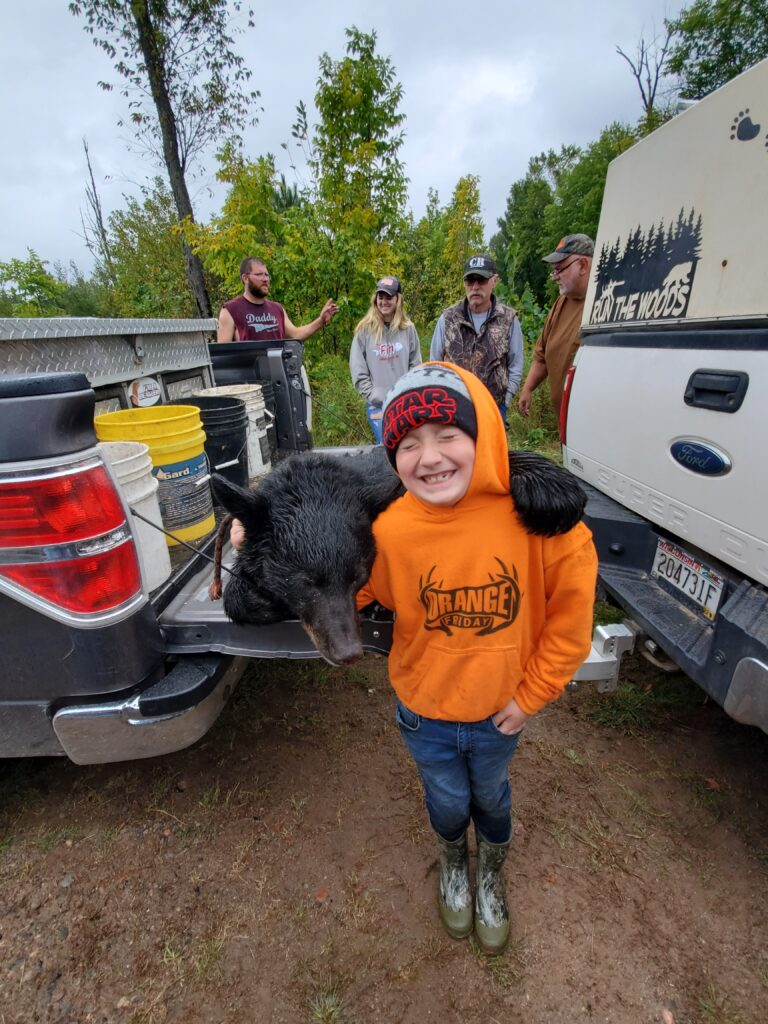 October 2021   SJ Monacelli   A boy & his bear   This is my first bear. I'm 7 years old and harvested the bear in the 2021 season hunting with hounds.